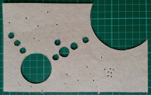 Piece of cardboard with spheres cut out to act as a stencil for applying developer/fixer to paper.