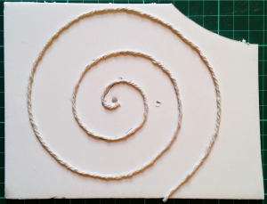 String spiral stuck onto foam board to act as a stamp for applying developer to the paper.