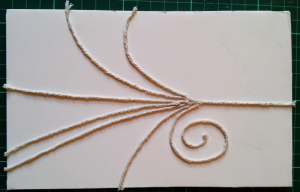 String trails stuck onto foam board to act as a stamp for applying developer to the paper.