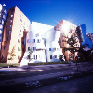 The vignetting effect of the pinhole creates a distinct bright spot in the center of the image. The pinhole also has a dramatic flare effect on the reflection of the sun on the windows which adds interest to the image .