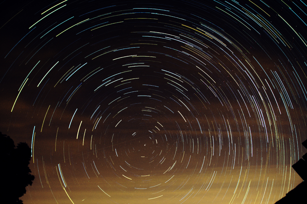 The basic star trail image with curve adjustments to reduce intensity of the sky glow. Due to the gradient, it is only possible to remove part of the sky glow